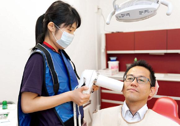 周術期室にてポータブル歯科用X線装置(モリタ社:ポートエックスⅢ)による撮影の様子。