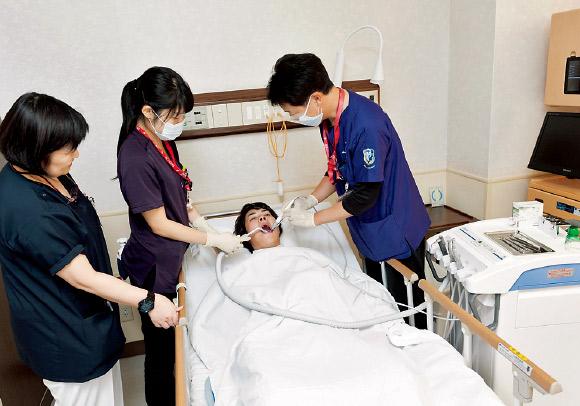 可搬式歯科用ユニットを使用した病室での治療の様子。
